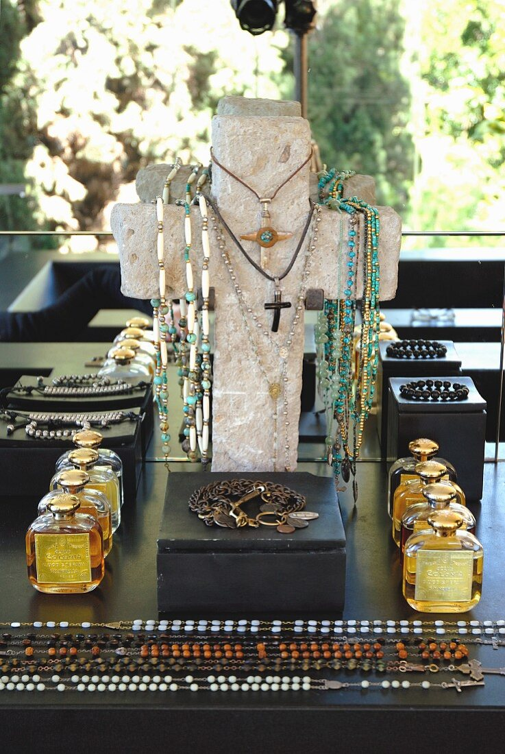Necklaces hung on cross-shaped jewellery stand behind black box, bottles of perfume and necklaces laid out on surface