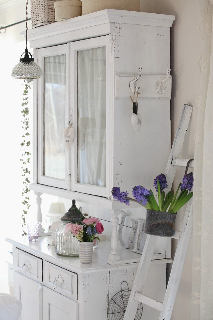 White, distressed dresser with shabby chic ornaments and blue hyacinths in pot hanging from ladder