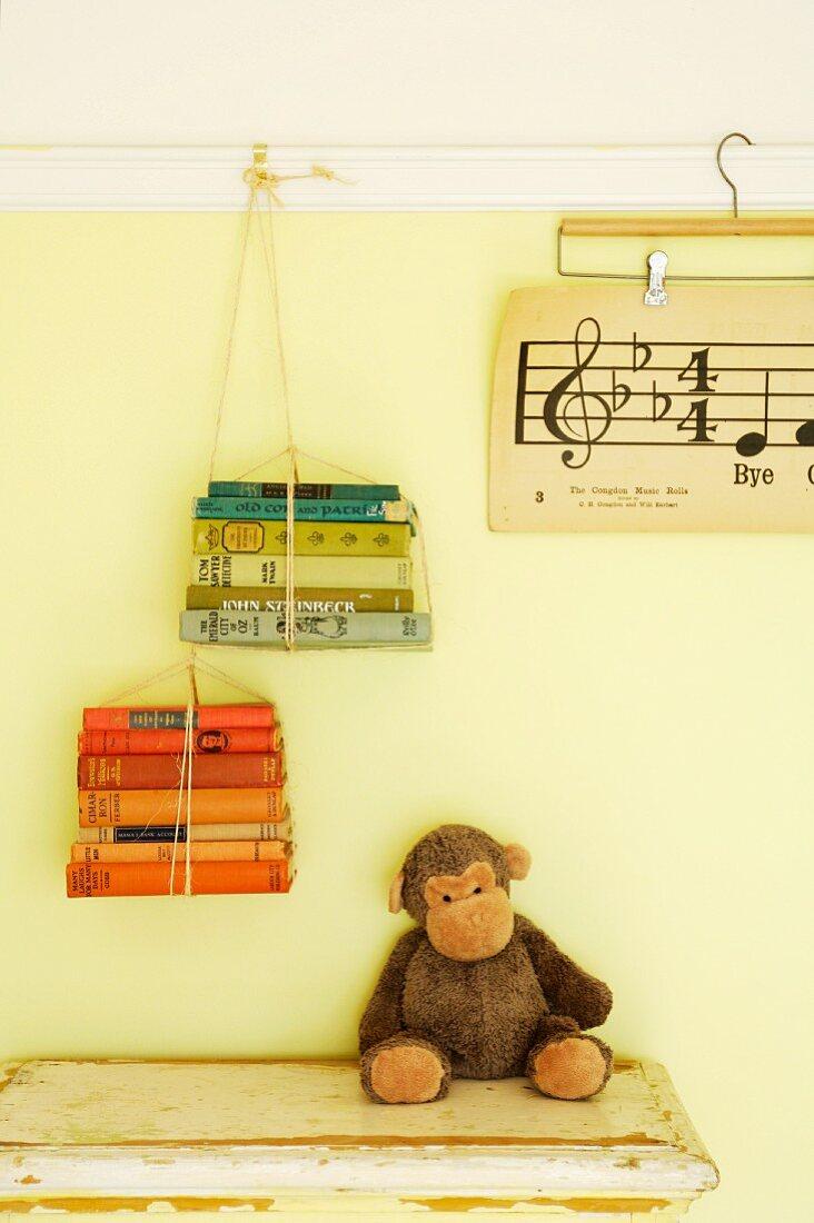 Selbstgemachtes Bücherregal: Zusammengebundene Bücher an der Wandleiste befestigt