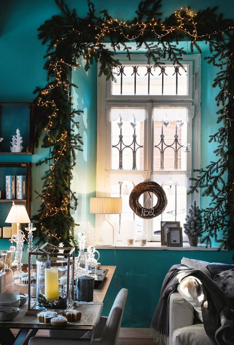 Christmas decorations with fairy lights around window frame behind ornaments on table