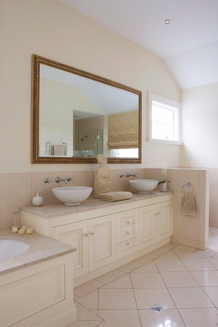 Waschtischunterschrank mit zwei Aufsatzbecken und Buddha-Figur, darüber gerahmtes Wandspiegel im Badezimmer