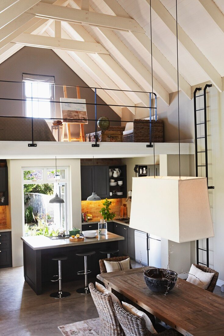 Renovated country house with exposed roof structure painted white - view down to white pendant lamp above dining table, kitchen area with counter below mezzanine in background