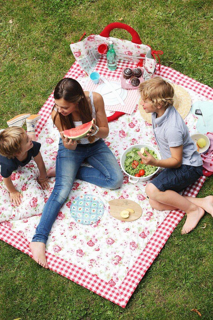 Children eating picnic on floral picnic blanket