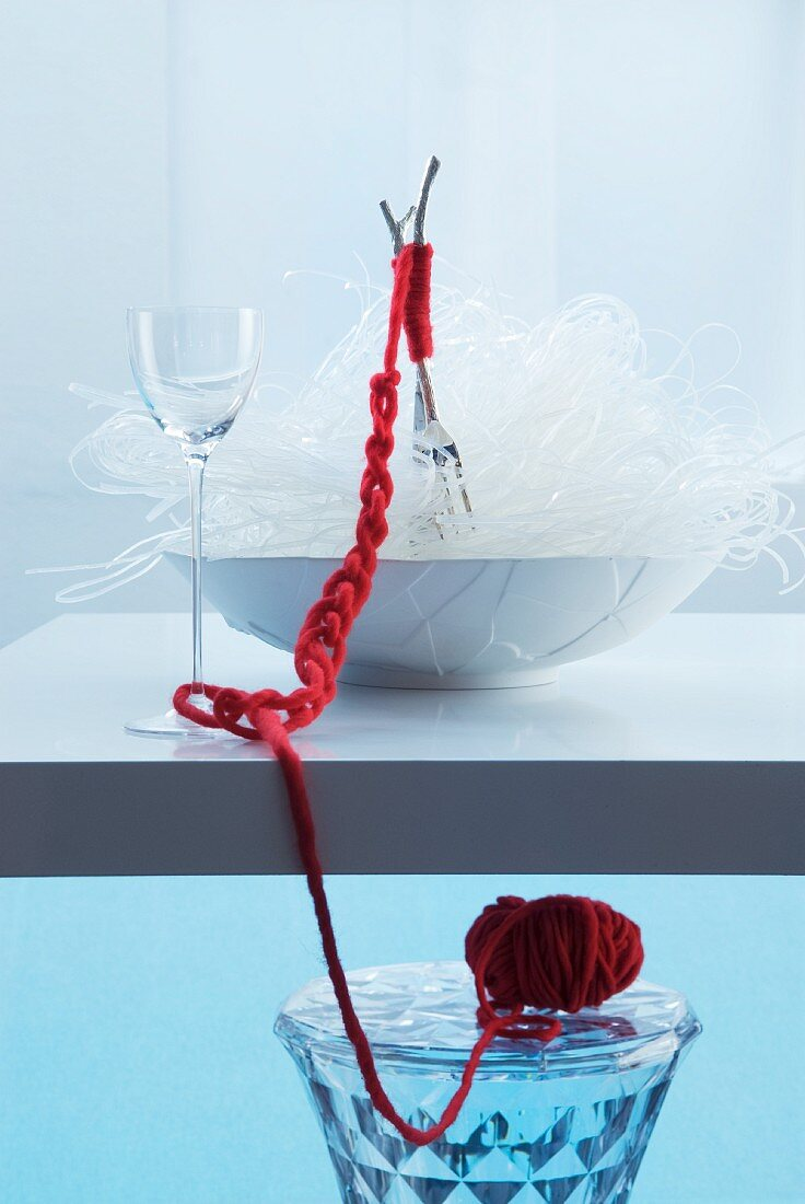 Oriental place setting: forks in bowl of glass noodles bound with red woollen yarn