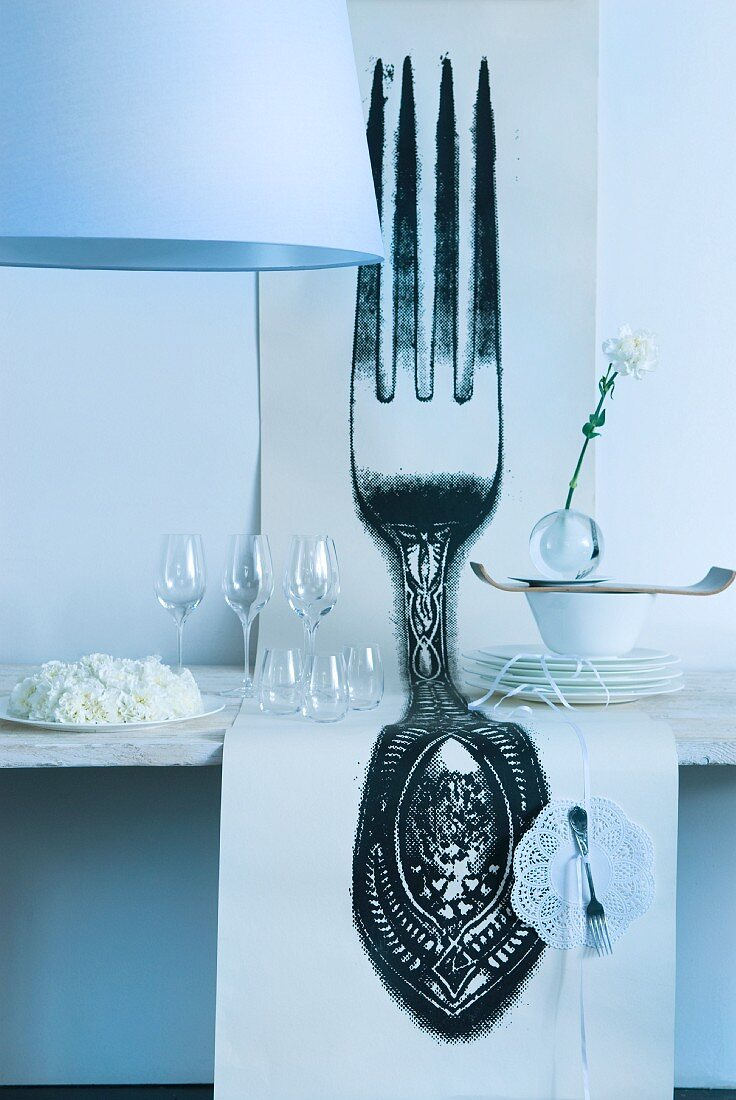 Length of wallpaper with enormous fork motif on wedding buffet table with cake, glasses and plates