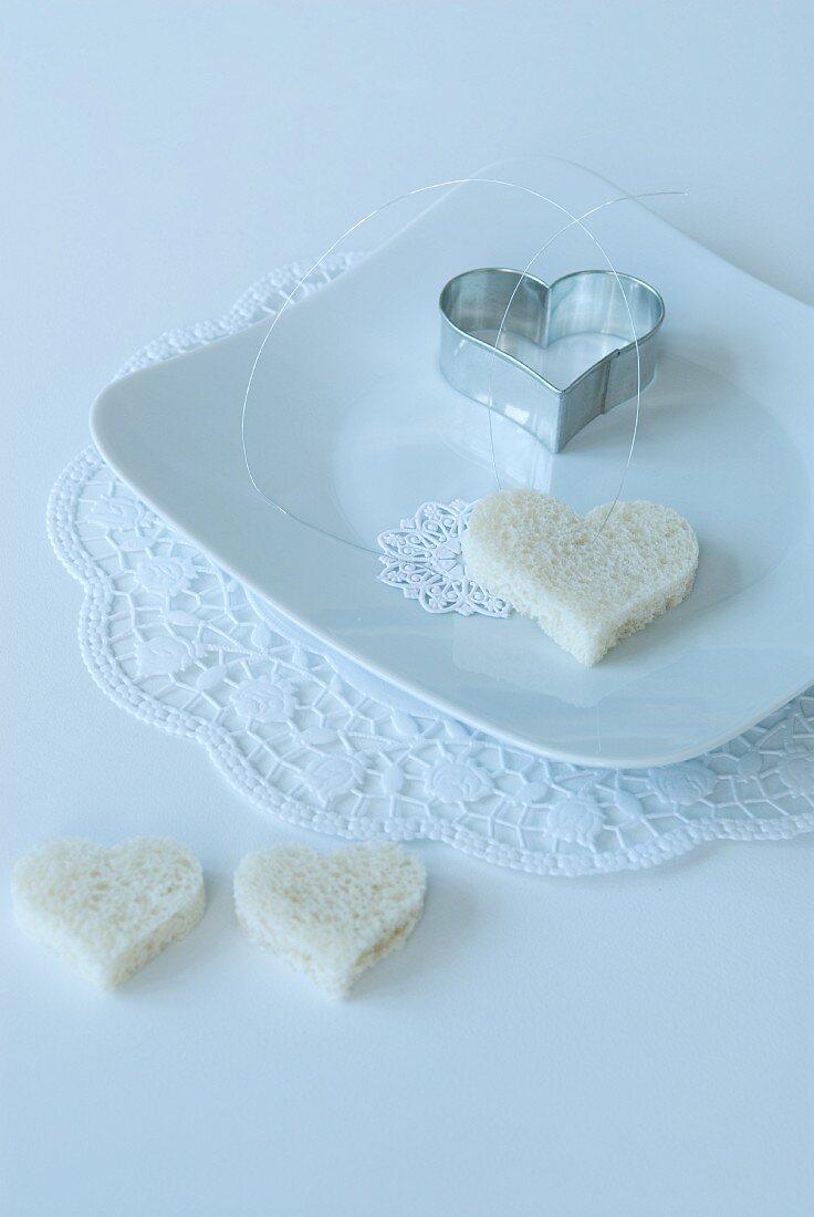 Weisses Gedeck mit herzförmigem Toast und Ausstecher auf Spitzendeckchen