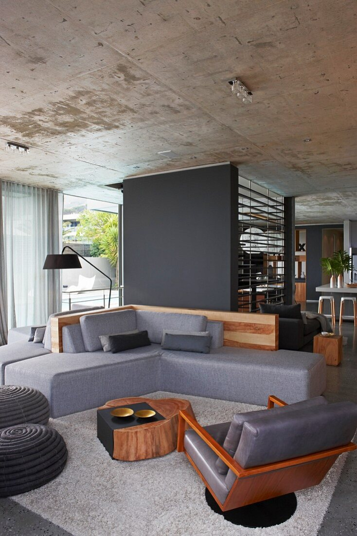 Elegant, comfortable, designer sofa combination with grey cushions in front of dark grey partition in open-plan living area with concrete ceiling