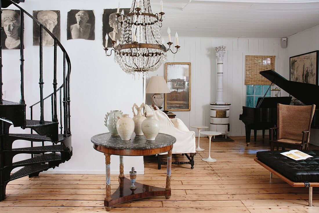 Furniture in a variety of styles from different periods in room with grand piano in far corner