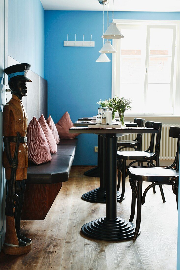 Restaurant with bistro tables, cushions on wooden bench, blue walls and wooden sculpture of man next to open door