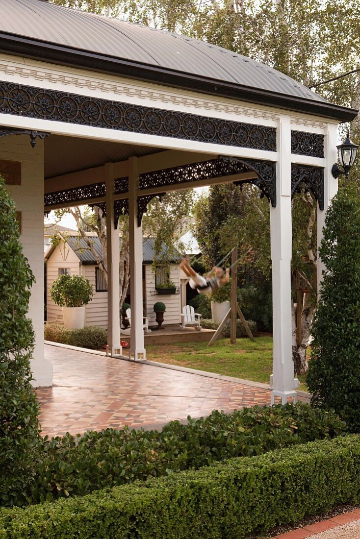 Porch with decorative frieze over veranda of Australian sandstone house built in 1890; play house and girl on swing in background