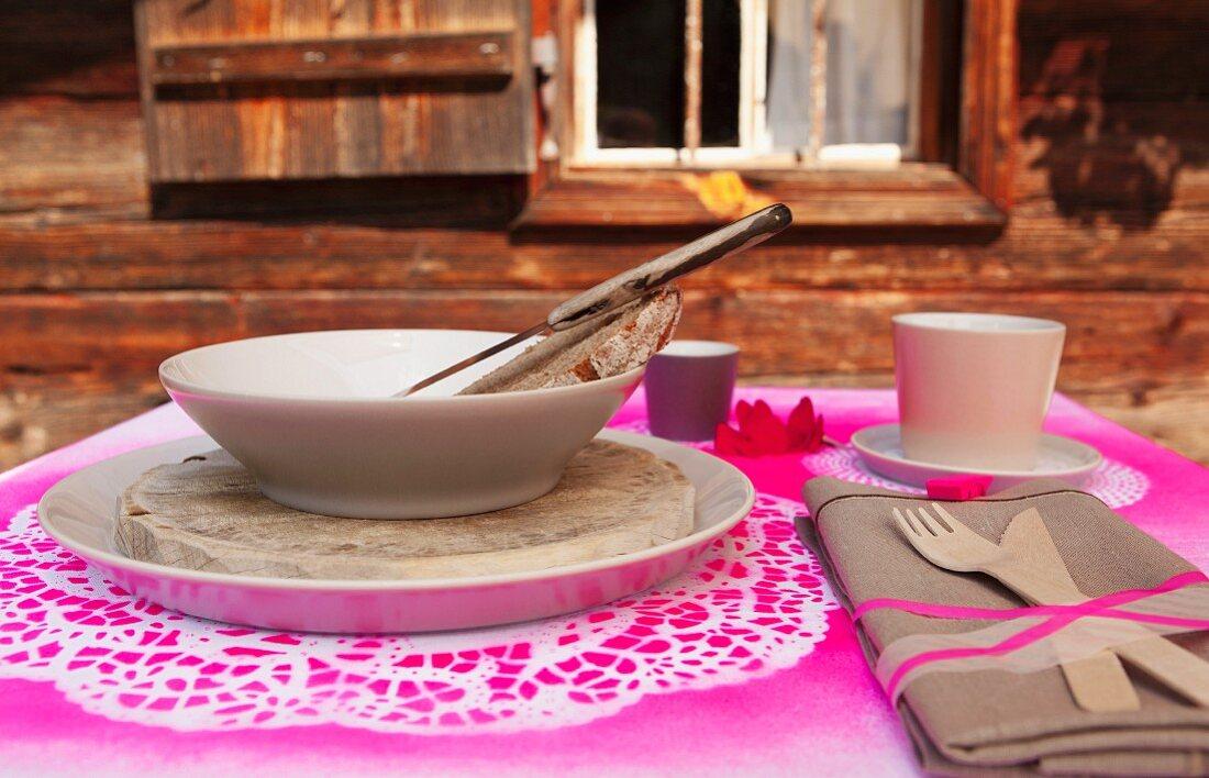 Gedeck mit Suppenschale und Holzbesteck an Stoffserviette gebunden auf gespraytem Tortenspitzen als Platzset vor Almhütte
