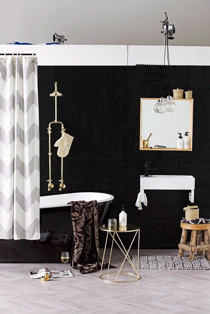 Black bathroom - metal side table, black glossy bathtub with shower head and mirror above sink against black wall