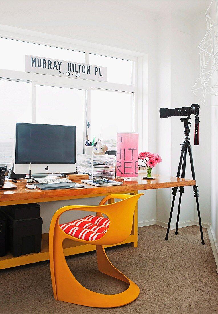 Schalenstuhl vor Schreibtisch mit Computer; daneben Kamera auf Stativ vor Fenster
