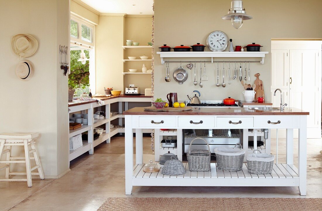 White island counter in open-plan, country-house kitchen with sand-coloured walls