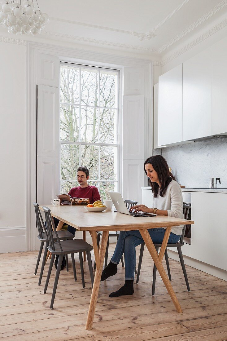 Young couple reading and working on laptop on table in white kitchen-dining room in period apartment with lattice window and wooden floor
