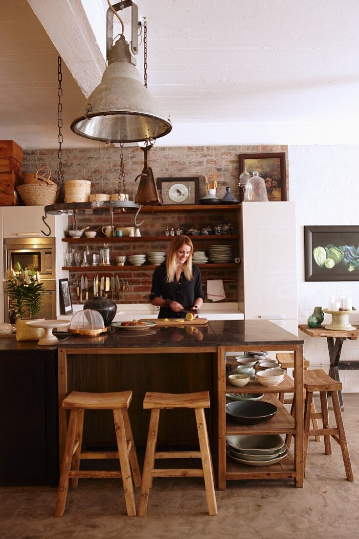 Woman standing behind counter in rustic, country-house-style kitchen with industrial lamps and ceramic crockery on open-fronted shelving
