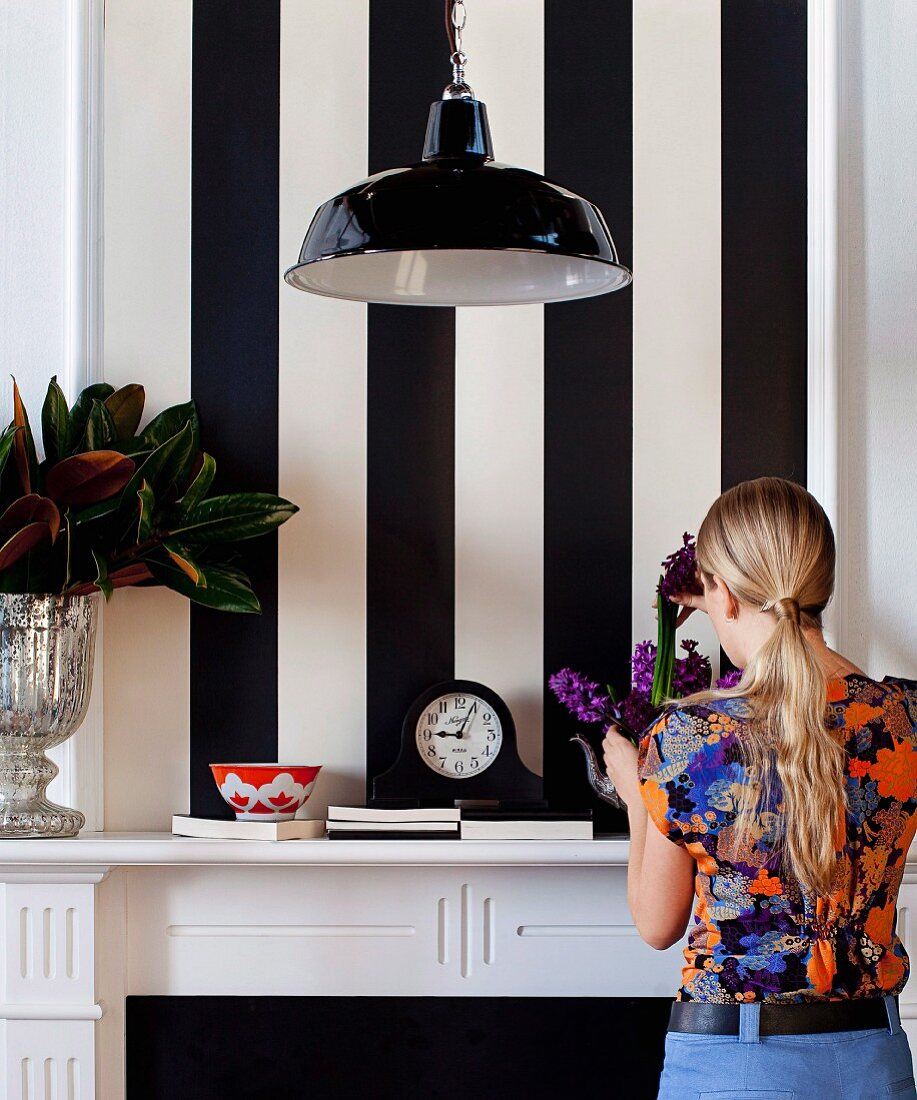 Woman arranging bouquet of hyacinths on mantelpiece against wallpaper with wide black and white stripes