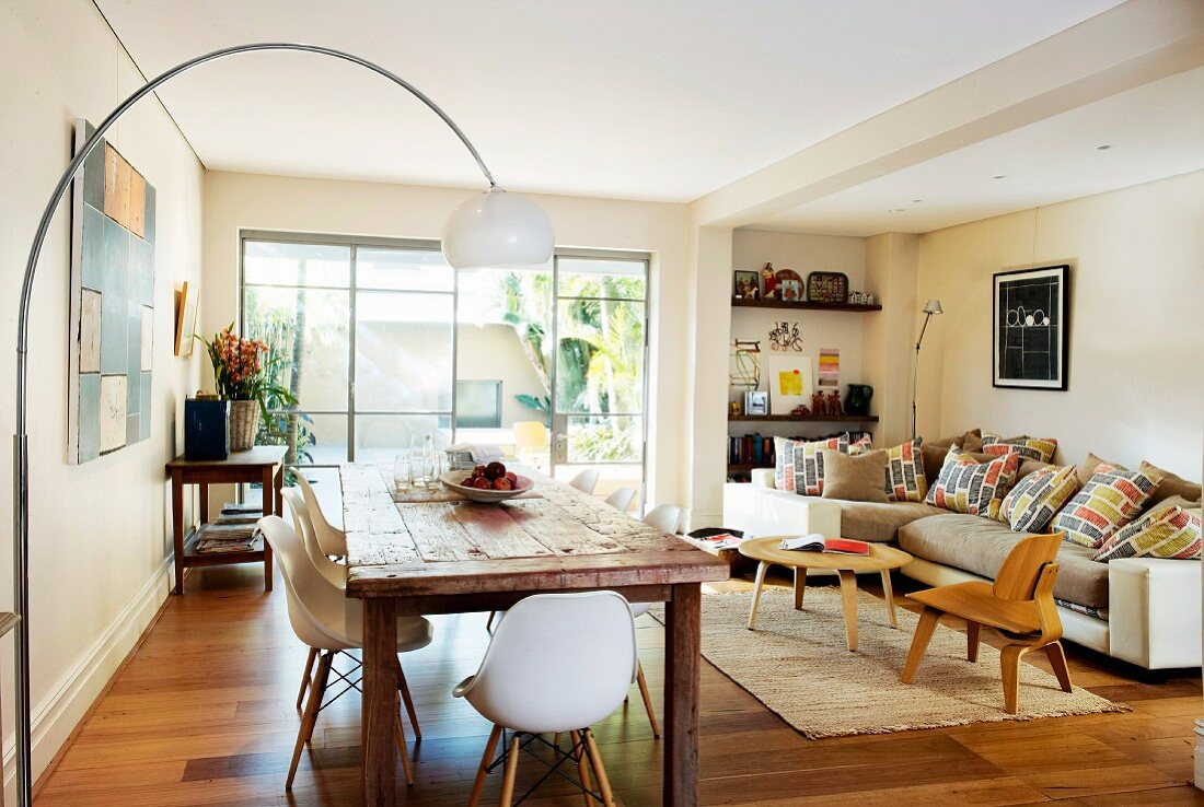 Living-dining room with classic, designer pieces, arc lamp over rustic wooden tables and 50s laminated wood furniture in front of corner sofa