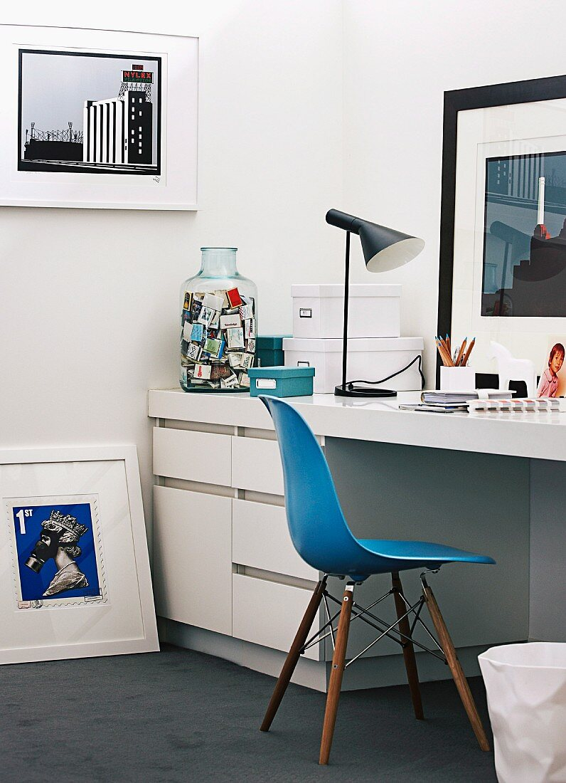 Collection of modern artworks in study with white fitted desk, blue Eames Chair and table lamp by Louis Poulsen