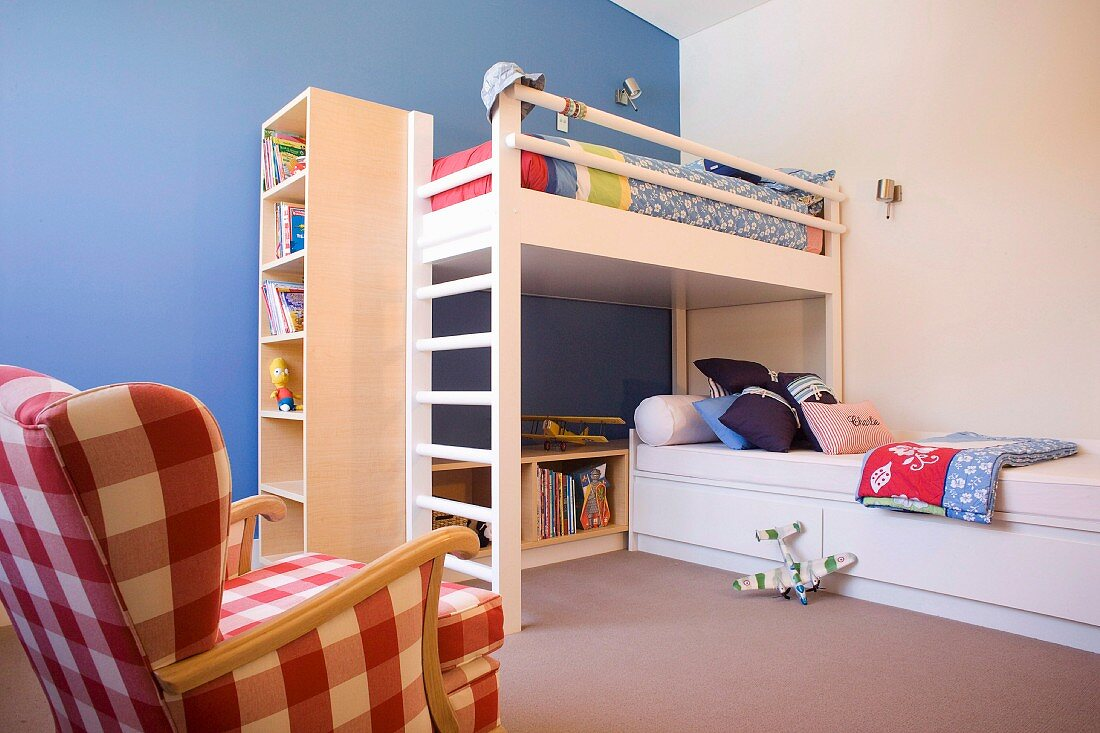 Loft bed with integrated shelving and single bed in modern, child's bedroom with one blue wall