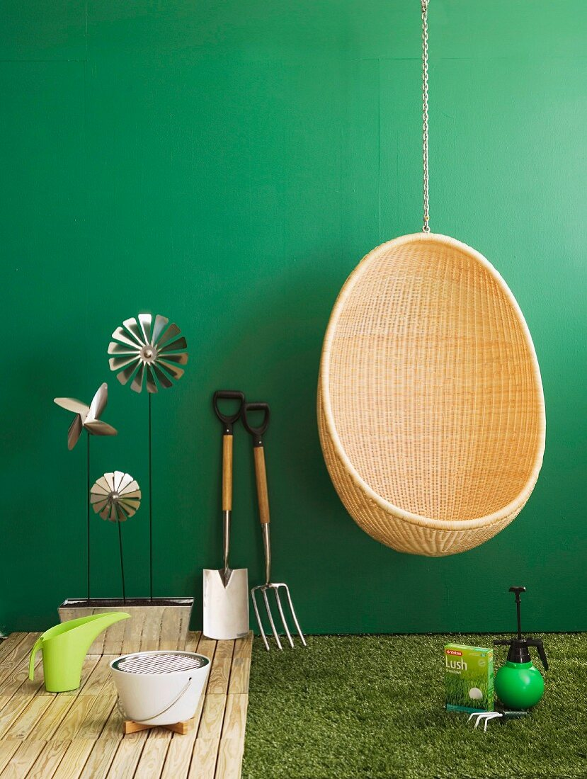 Wicker hanging chair next to gardening utensils and garden ornaments arranged on wooden decking and artificial lawn against green wall
