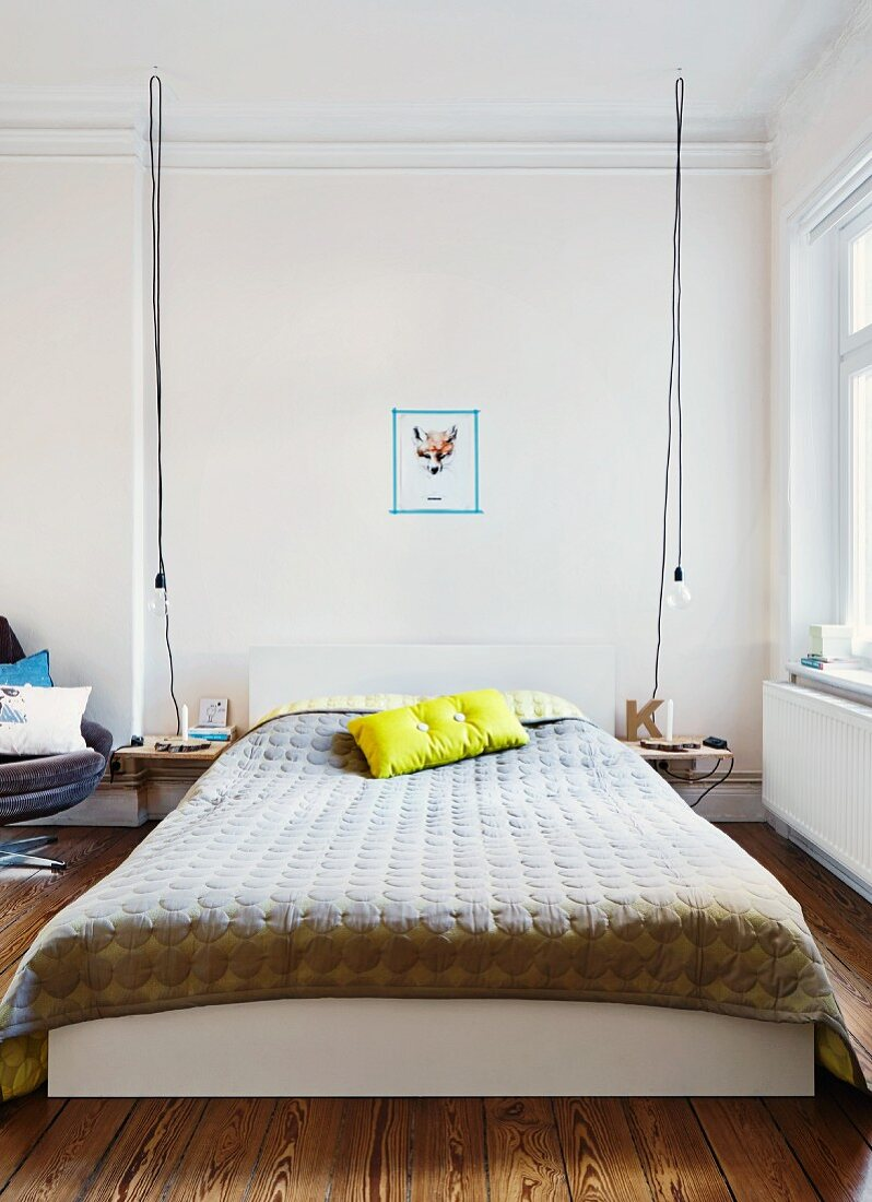 Bed with Danish bedspread and scatter cushion flanked by DIY bedside tables and light bulbs hanging from long cables