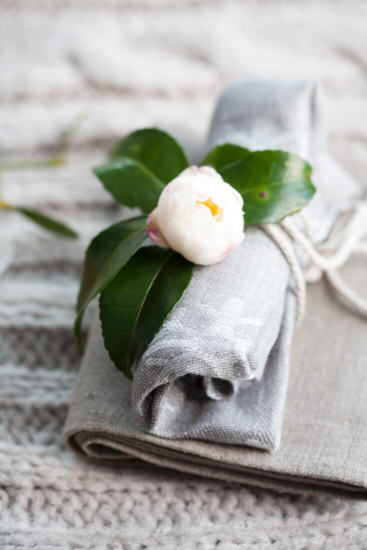 White gardenia decorating rolled linen napkin