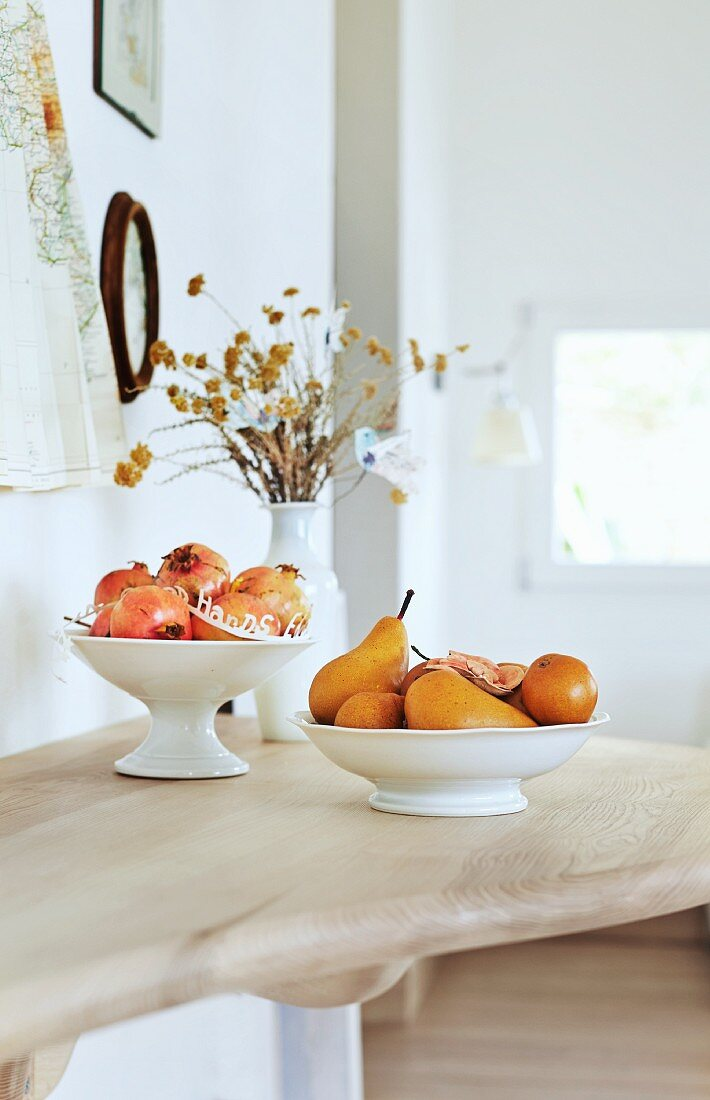 White ceramic bowls of fruit and vase of dried flowers on wooden surface