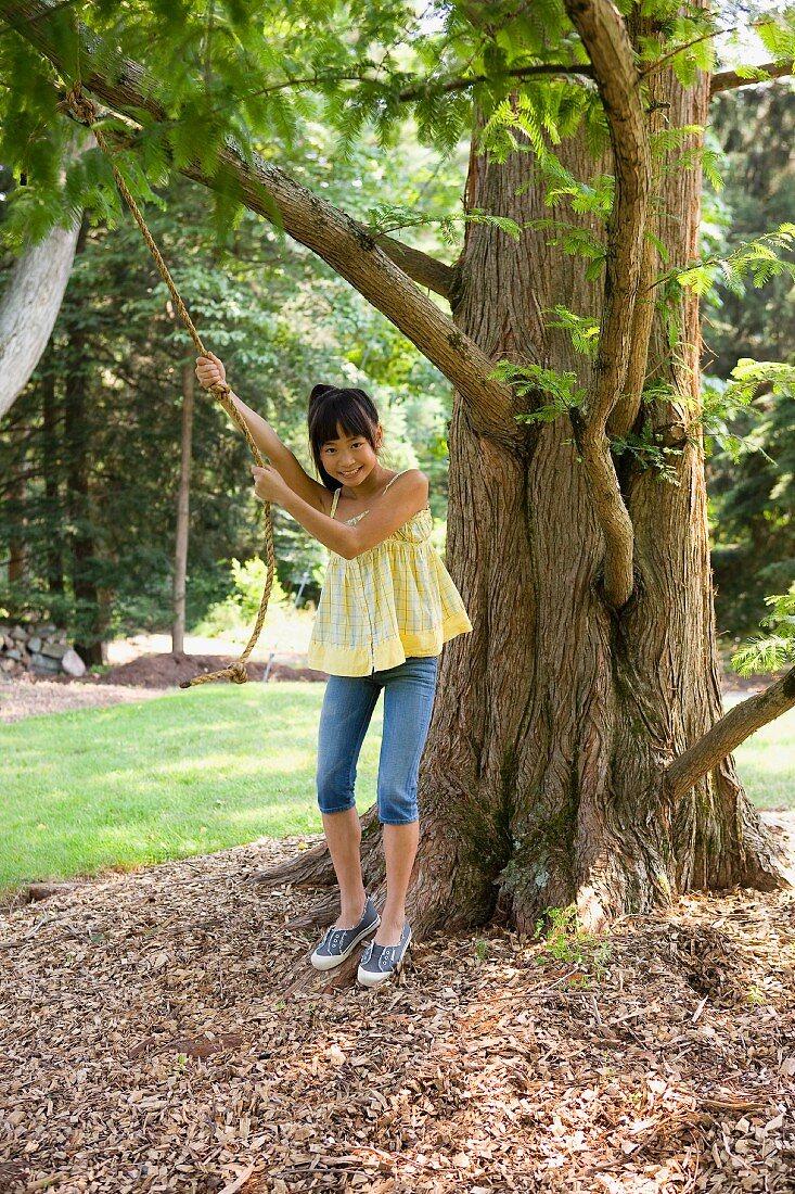 Mädchen mit Schwungseil am Baum