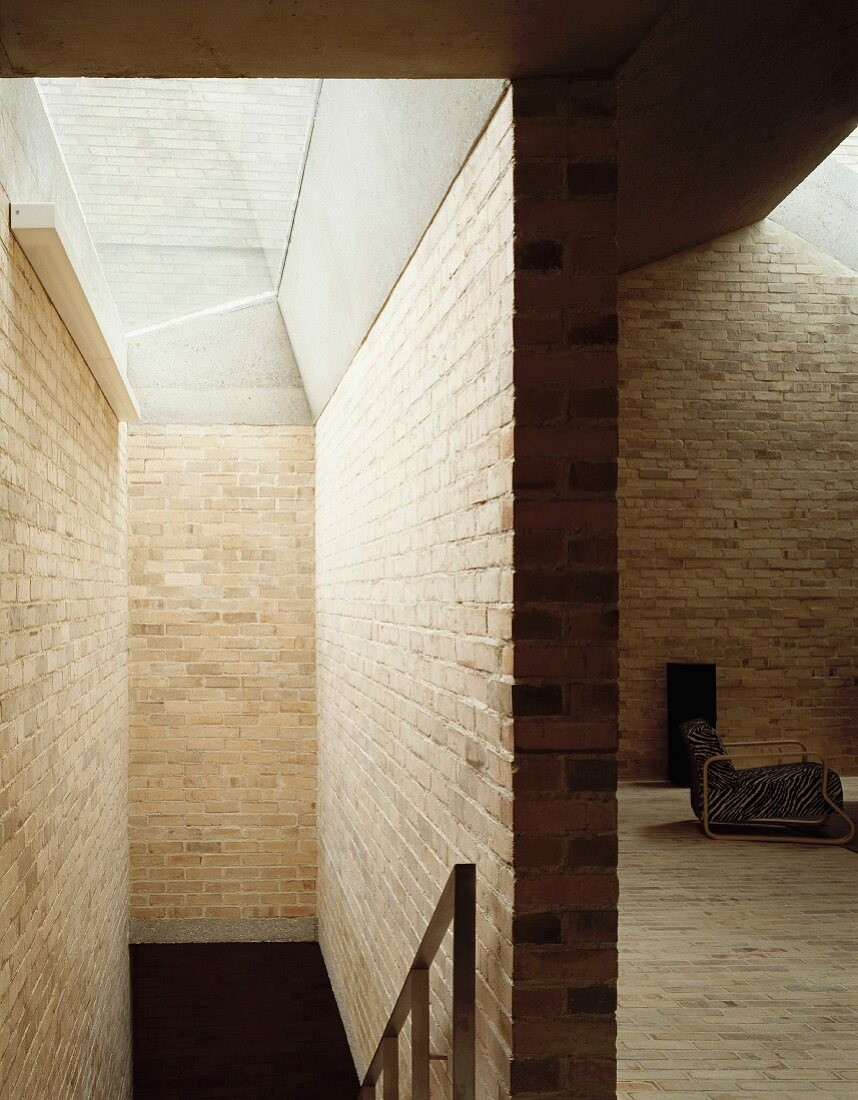 Modern house with brick walls and view through a passage to an armchair