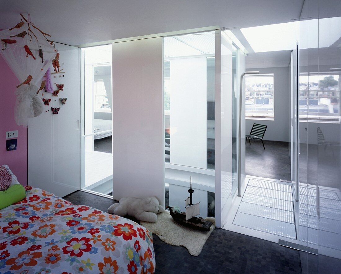 Flowered bed linen in child's room with view through ceiling-height window elements into stairwell and living room