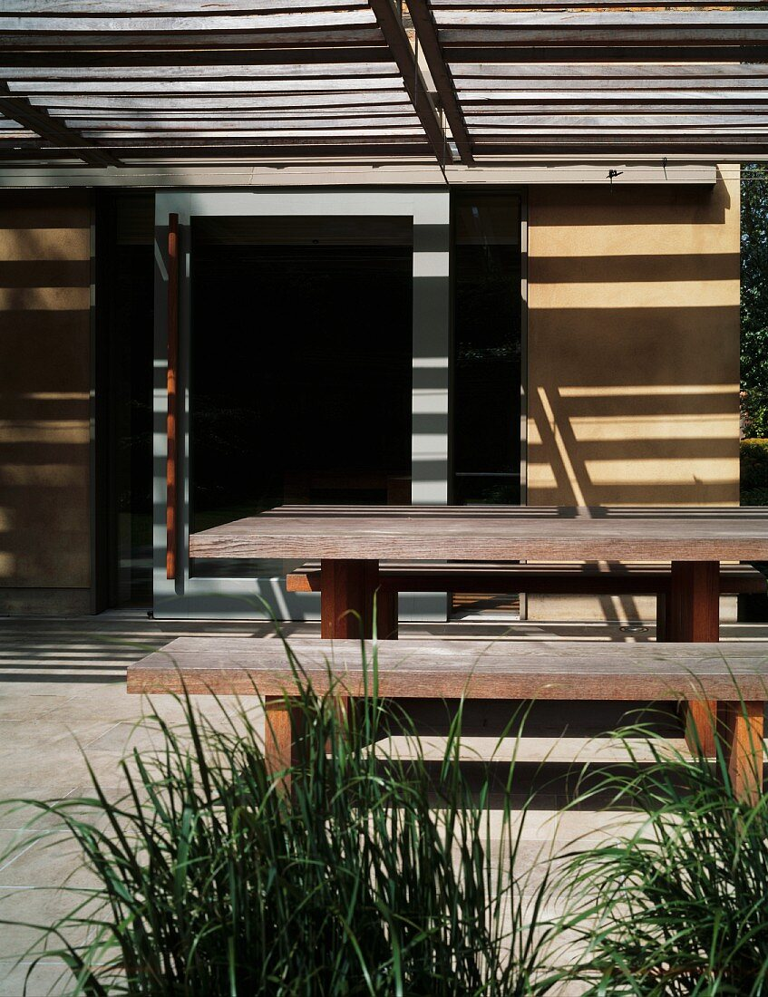 Pattern of light and shade on plain, rustic dining area under wooden pergola