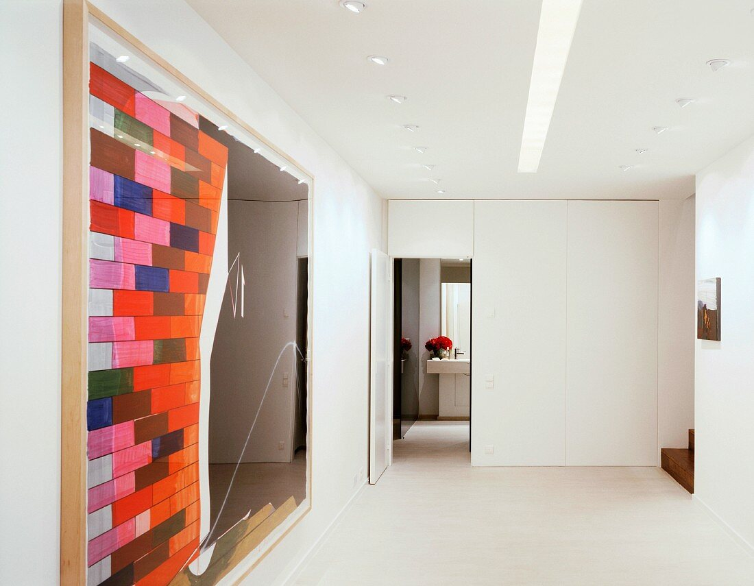 A modern picture next to an open door in a white-painted, minimalistic anteroom