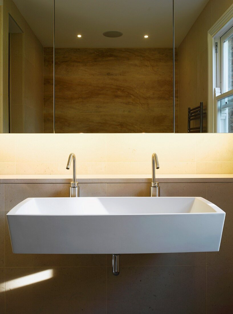 Large sink with two designer tap fittings under mirrored cupboard with indirect lighting