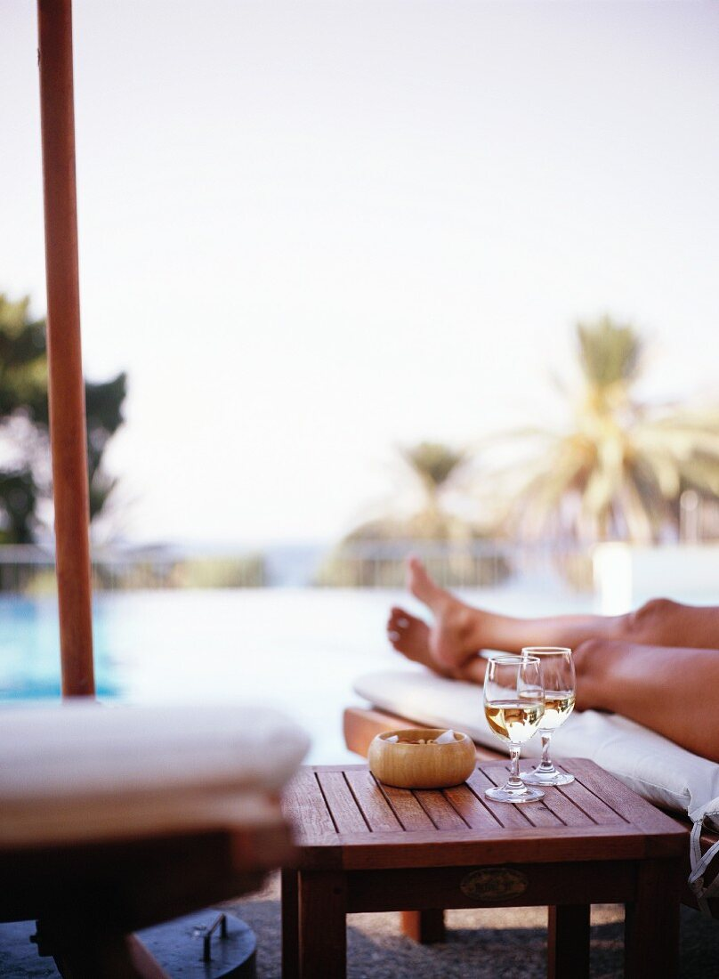 Two glasses of white wine on side table by swimming pool