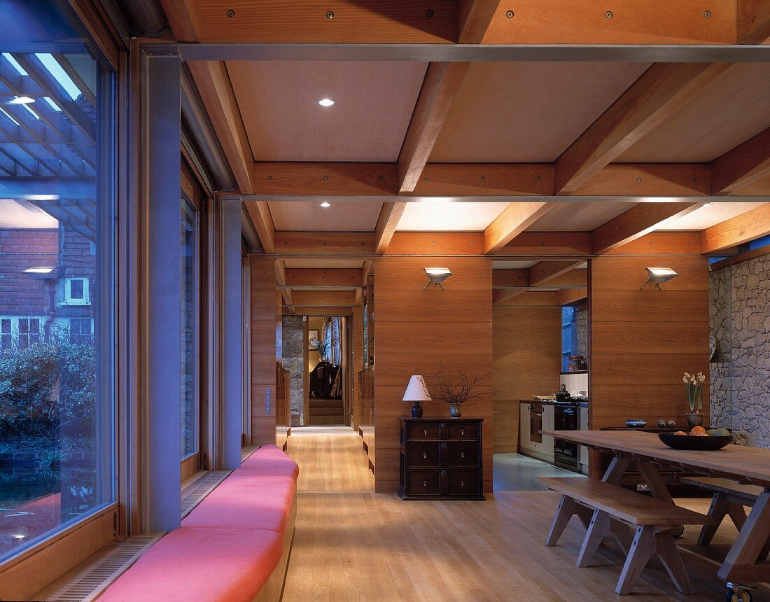 Open-plan dining room with wood-cladded ceiling and glass wall facing garden