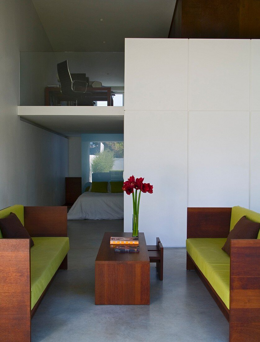 Sofa with lime green cushions and wooden frame and matching coffee table in modern interior with view of gallery and open doorway leading to bedroom