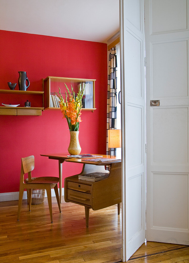 View of study with original 50s furnishings and rich red back wall through half-opened folding door