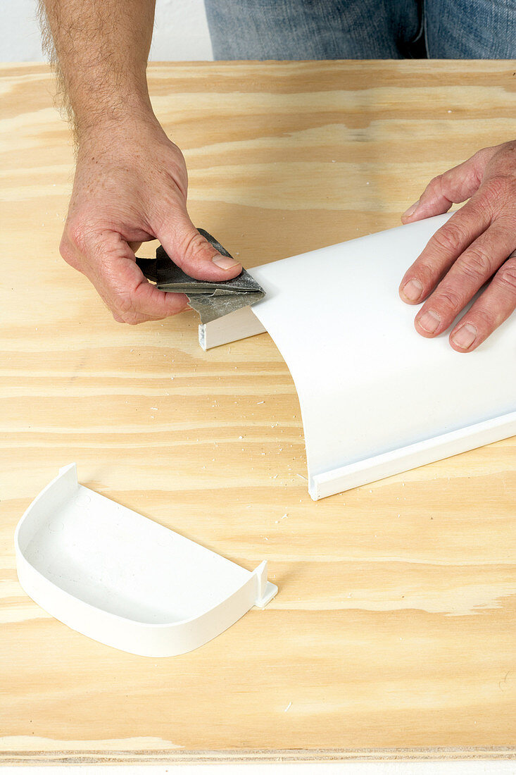 DIY - man sanding corners of a plastic container