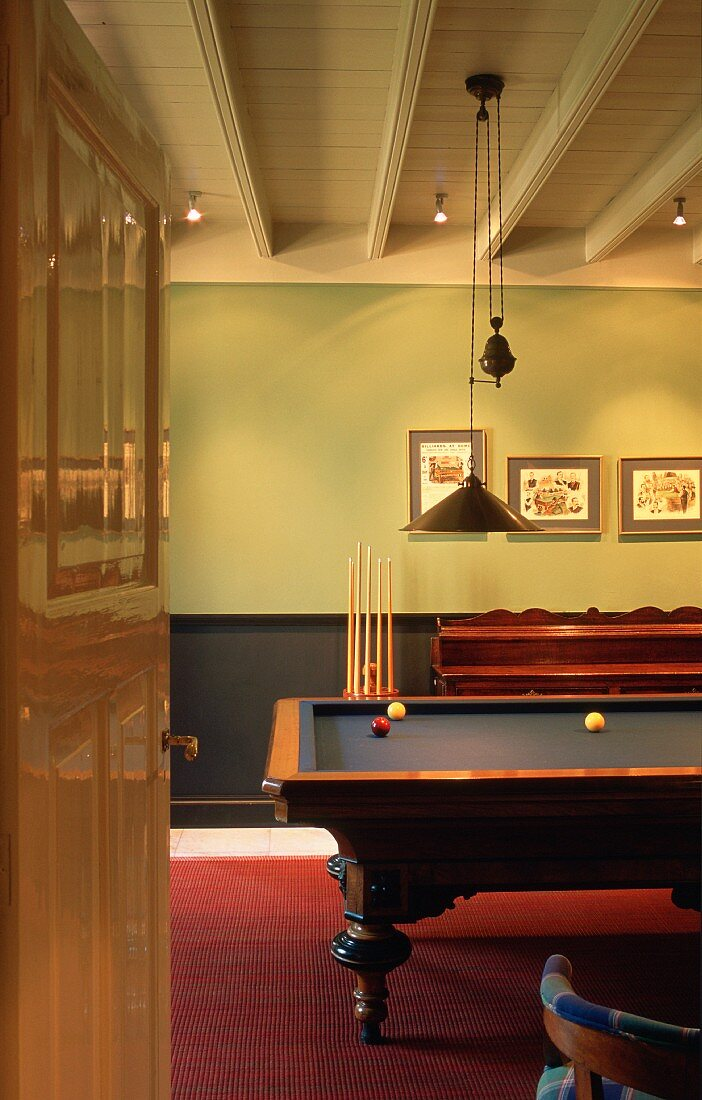 View through open door of wooden billiard table in simple room with white wooden ceiling and red floor