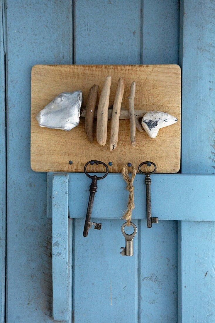 Hand-crafted key holder with fish motif made from driftwood and limestone pebbles