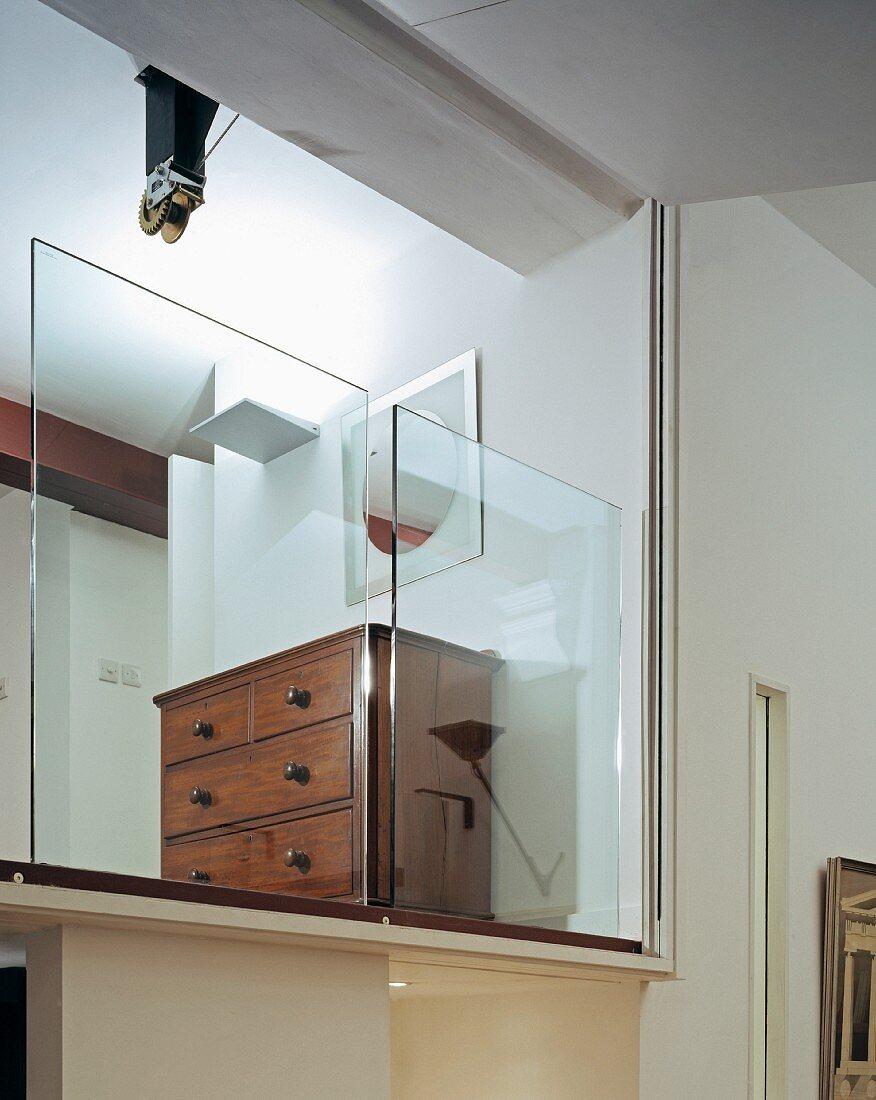 Antike Kommode hinter halbhohen Glaspanelen auf Galerie