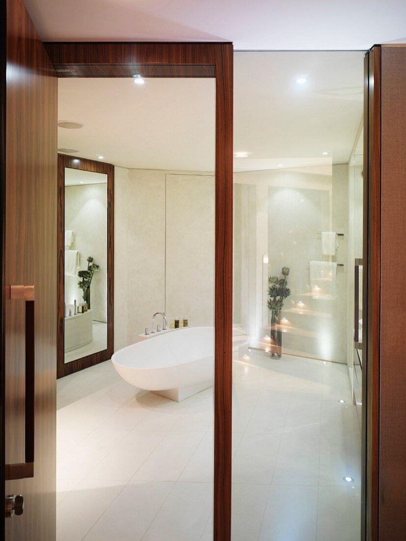 View through open wood and glass door into white designer bathroom