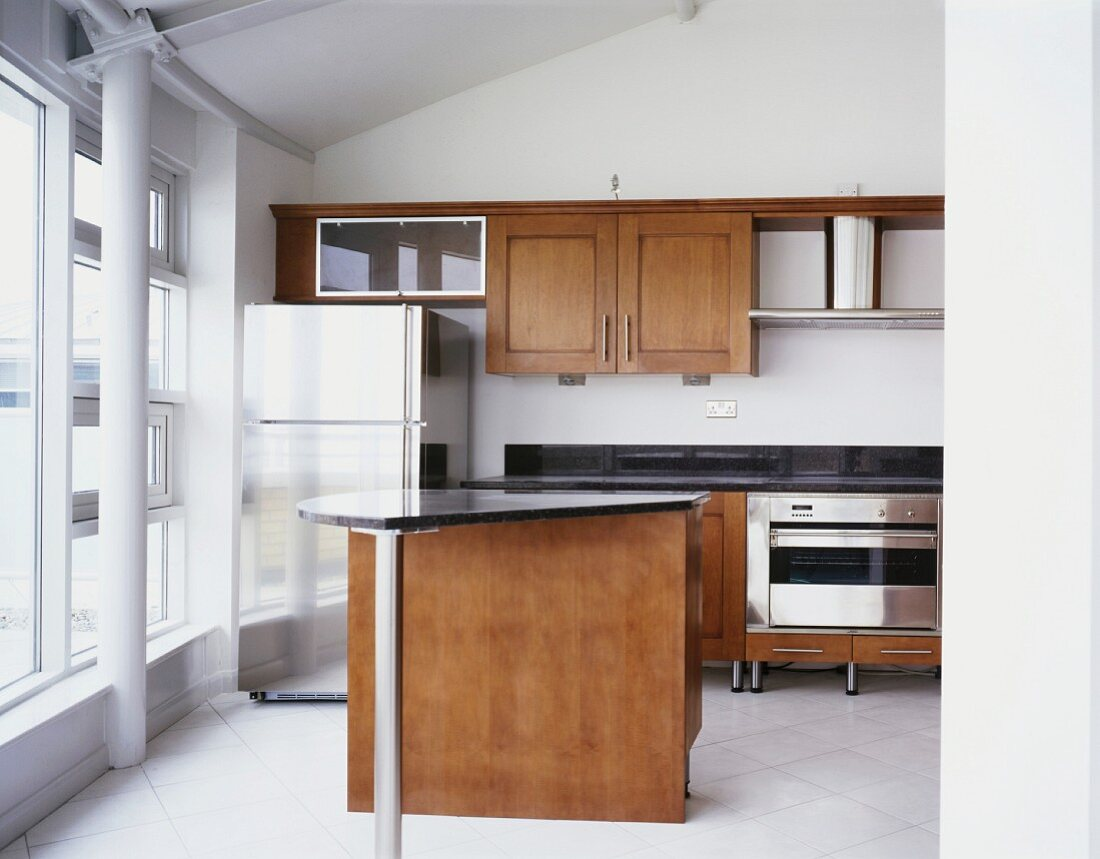 Modern fitted kitchen with black granite counter top, stainless steel refrigerator and wooden doors
