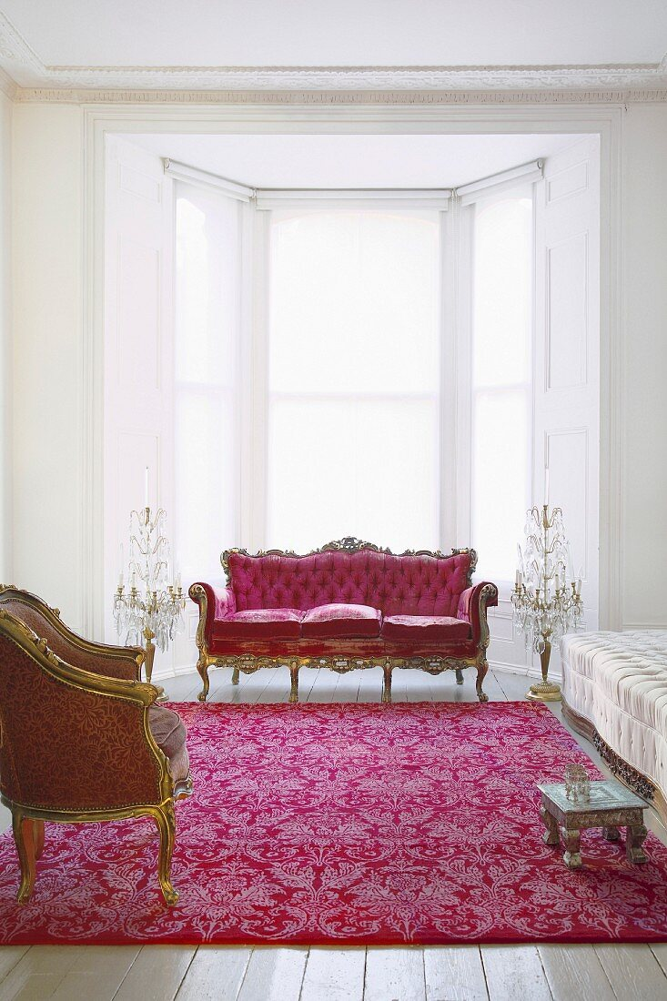 Red and gold Rococo chair and sofa in white room with traditional ambience