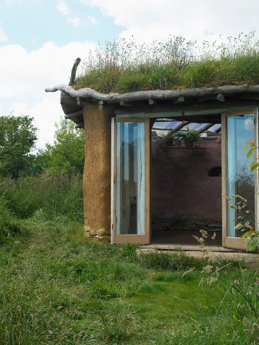 Open terrace door leading into clay house with organic design and green roof