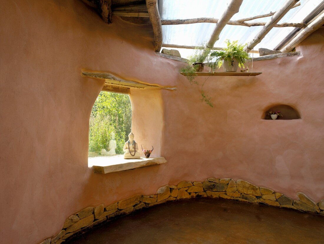 Clay house with organic lines, skylight and Buddha statue in frameless window aperture