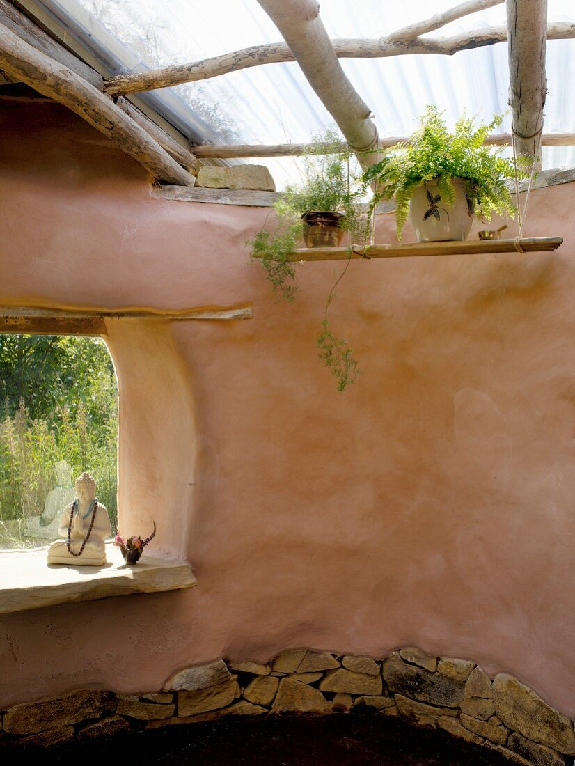 Clay house with organic lines, simple skylight structure and Buddha statue in frameless window aperture