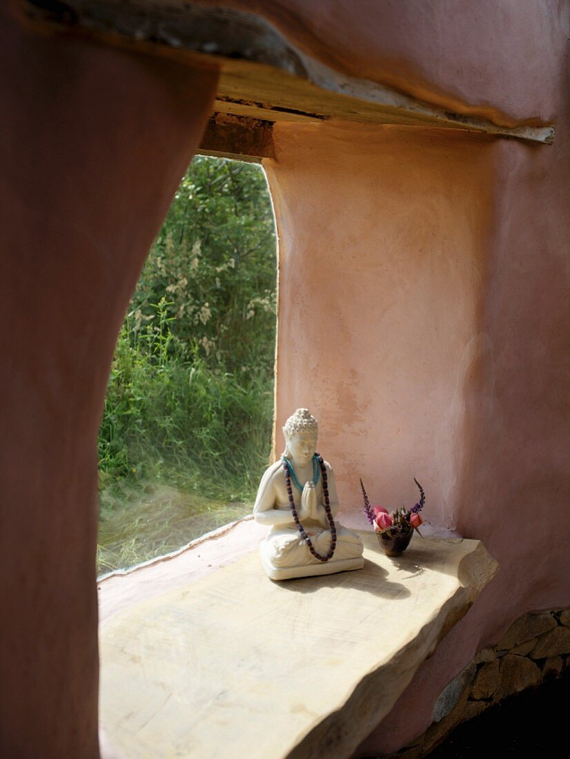 Praying Buddha figure in frameless window of clay house with organic lines