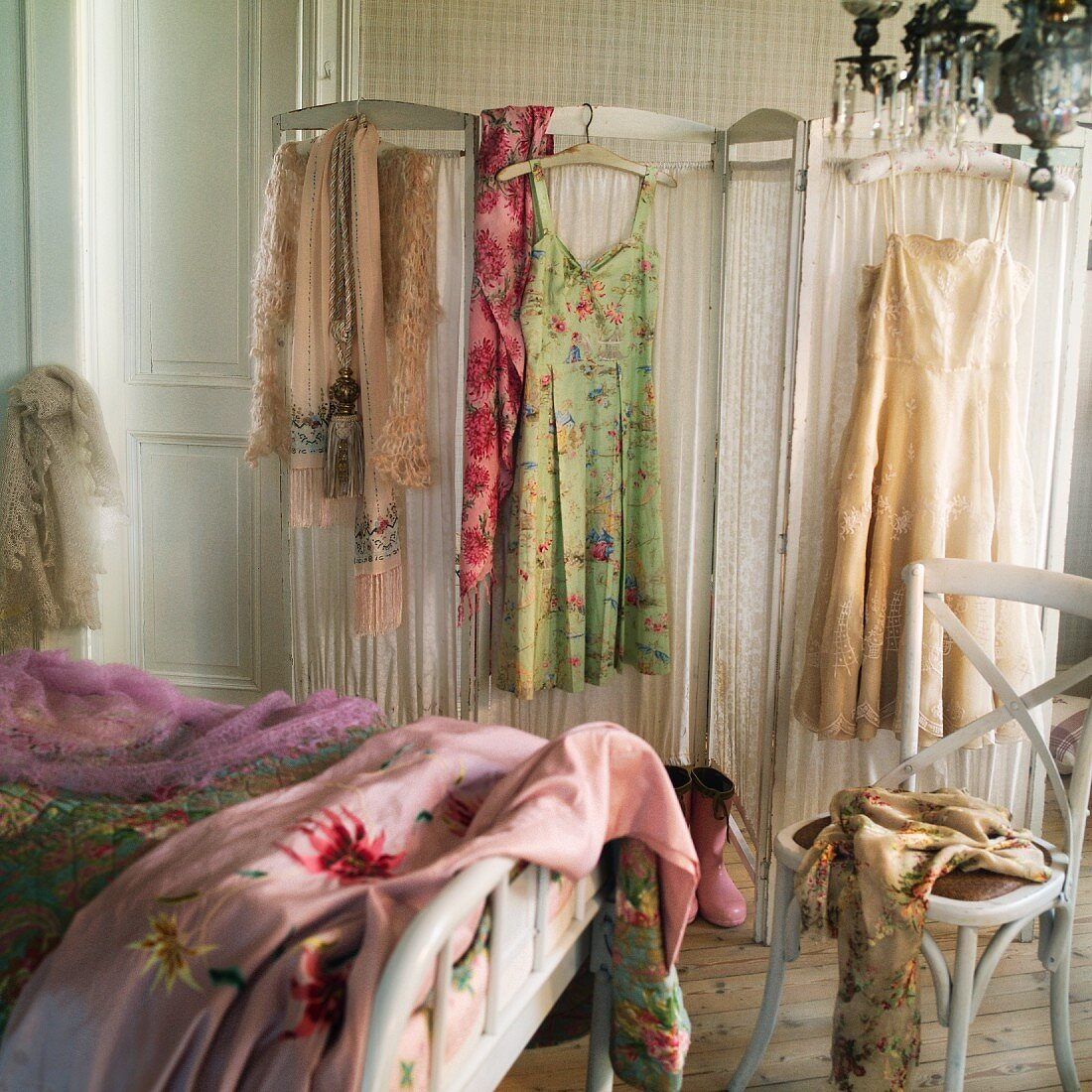 Boudoir with vintage ladies clothing hanging on a screen